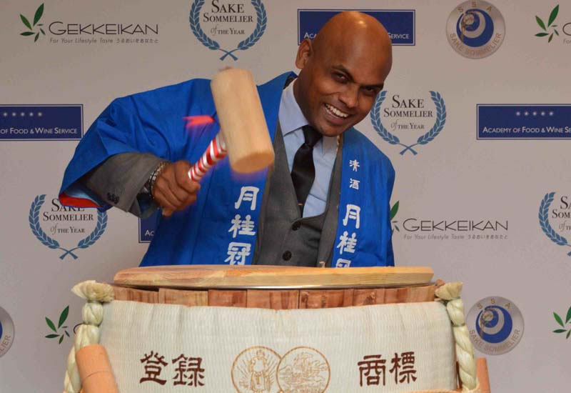 Rajan performing the ancient ritual of breaking open a ceremonial cask of sake.