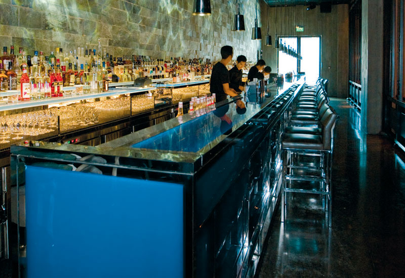 NIGHT MODE: The blue glass rectangular bar features a retro-lighted top. The cleaved slate on the back wall with rippled lighting gives a night-time m