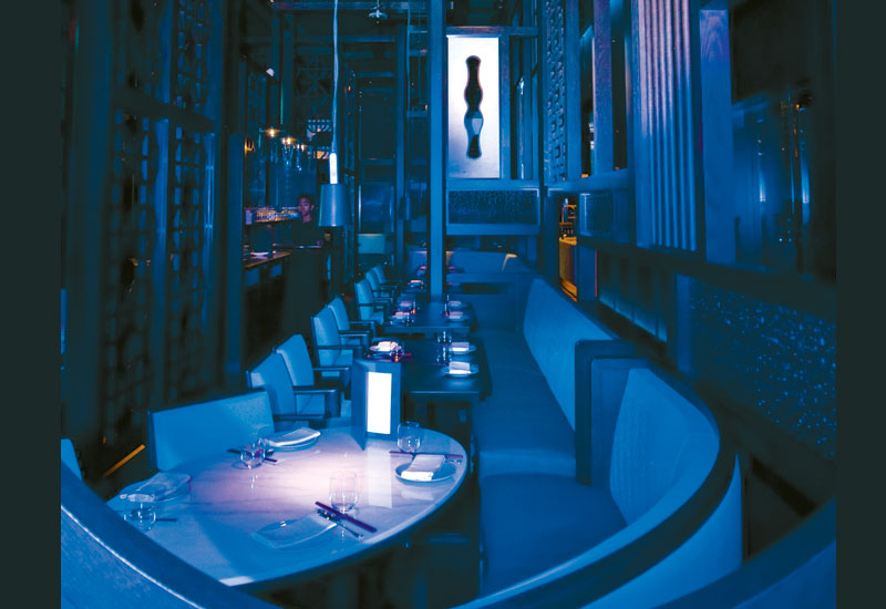 THE CAGE: The main dining wood work structure is surrounded by blue glass retro lighted in a brushed stainless steel frame.