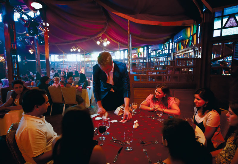 A roving magician entertains diners at  Dubai Festival Centre's House of Illusions.